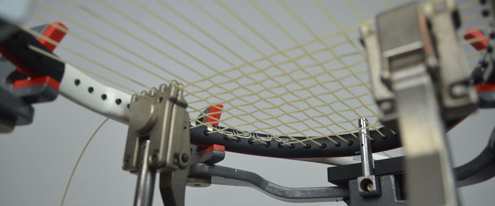 A photograph from below a tennis racquet on a stringing machine being strung with Tecnifbire X-One Biphase.