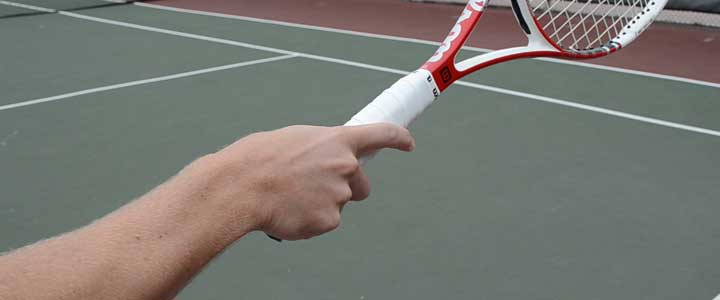 A photograph showing the proper serve grip with the index finger slightly raised on the handle.