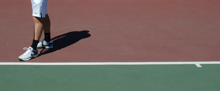 A photograph showing where to stand along the baseline for the correct doubles serve stance.