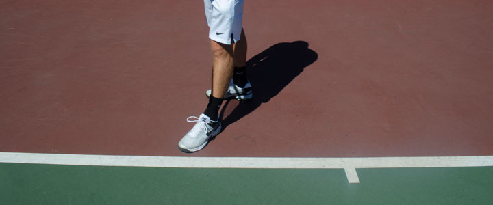 A photograph showing where to stand along the baseline for the correct singles serve stance.